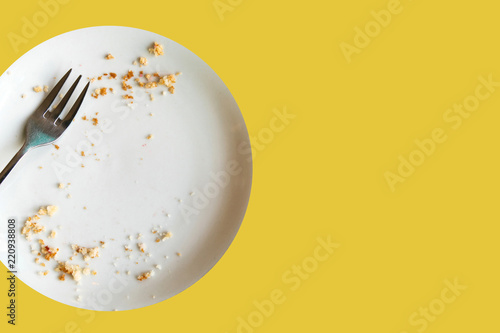 Fotografía  Empty plate with crumbs after eating on a yellow background