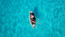 Aerial Drone Bird's Eye View Photo Of 2 Women Canoeing In Tropical Beach Of Voutoumi, Antipaxos Island, Greece