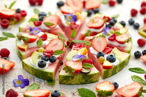 Watermelon pizza with various fresh fruits with the addition of cream cheese, mint and edible flowers. A delicious fruity dessert, the concept of healthy eating