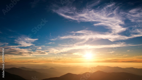Silhouettes of mountains on background of sunset sky