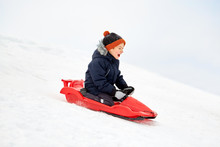 Childhood, Sledging And Season Concept - Happy Little Boy Sliding On Sled Down Snow Hill Outdoors In Winter