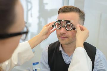 man wearing phoropter for eye test