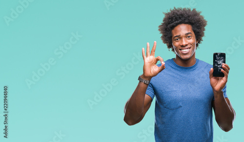 Fototapeta Afro american man holding broken smartphone over isolated background doing ok sign with fingers, excellent symbol obraz
