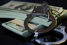 Handcuffs And Money In The Darkness. Concept Of Business Fraud And Corruption.