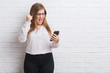 Young adult business woman over white brick wall sending message using smartphone annoyed and frustrated shouting with anger, crazy and yelling with raised hand, anger concept