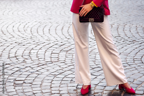 Fashion details: woman wearing white wide-leg trousers, pink blazer, wrist watch, pointed toe shoes, holding velvet violet quilted bag, posing in street of european city Wallpaper Mural