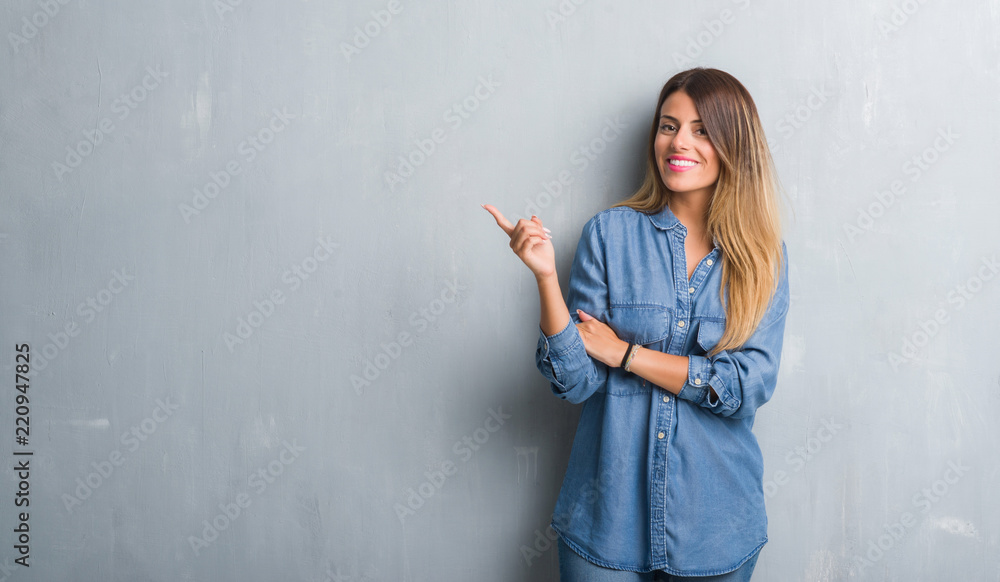 Fototapeta Young adult woman over grunge grey wall wearing denim outfit with a big smile on face, pointing with hand and finger to the side looking at the camera.