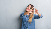Young Adult Woman Over Grunge Grey Wall Wearing Glasses Smiling In Love Showing Heart Symbol And Shape With Hands. Romantic Concept.