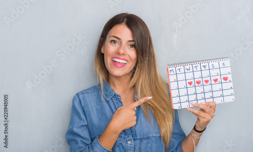 Cuadros en Lienzo Young adult woman over grey grunge wall showing period calendar very happy point