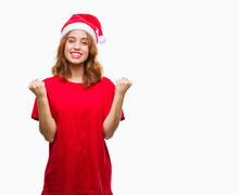 Young Beautiful Woman Over Isolated Background Wearing Christmas Hat Celebrating Surprised And Amazed For Success With Arms Raised And Open Eyes. Winner Concept.