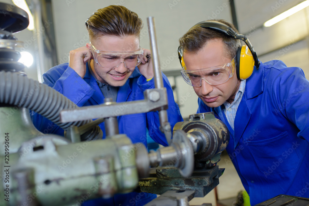 Fototapeta Apprentice protecting ears from noisy machine