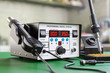Soldering iron digital station on the workplace. 3d render