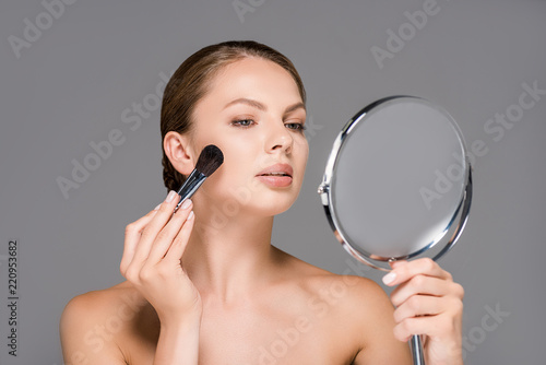 Fototapety, obrazy: portrait of young woman looking at mirror and applying blush isolated on grey