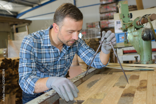 artisan measuring a plank