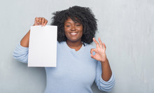 Young African American Woman Over Grey Grunge Wall Holding Blank Paper Sheet Doing Ok Sign With Fingers, Excellent Symbol