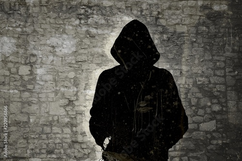 Cuadros en Lienzo Male black and white figure with hood on stone wall background
