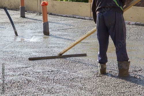 Worker Leveling Fresh Concrete Slab With A Special Wooden Working Tool