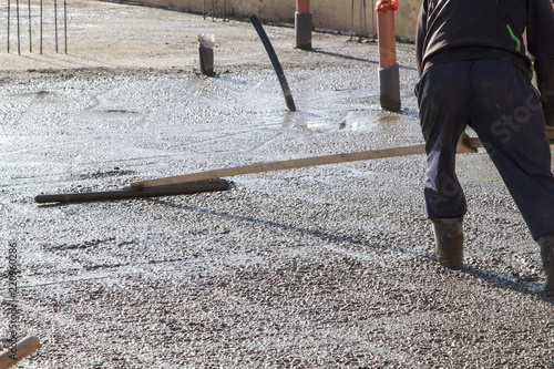 Worker In Rubber Boots Stands Uncluttered Cement And Leveling The Surface Of Base Plate