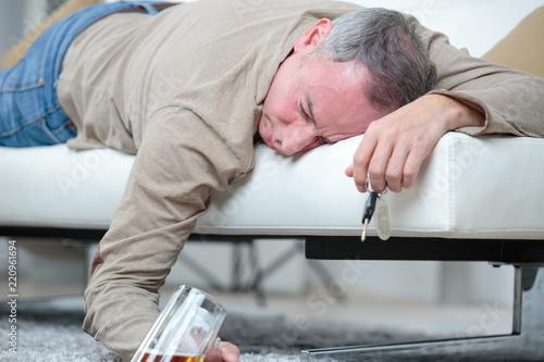 Fotografija  senior man sleep with glass of beer on the sofa