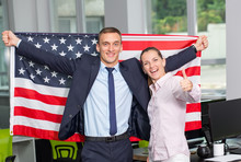 Successful Couple Man And Woman With The United States Flag Of American. Happy Business People With The US Flag In The Office. Patriots. Thumbs Up.