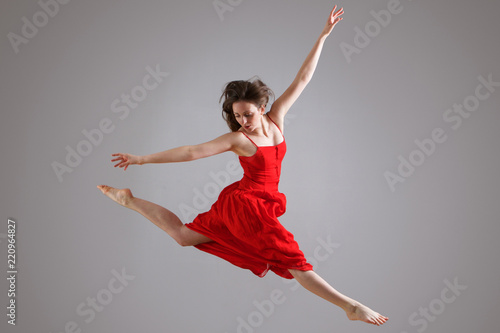 Obraz na plátně  elegant dancer in red dress jumping against gray background