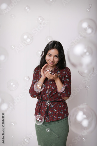 beautiful girl among the glass balls one of which she holds in her hands Canvas Print
