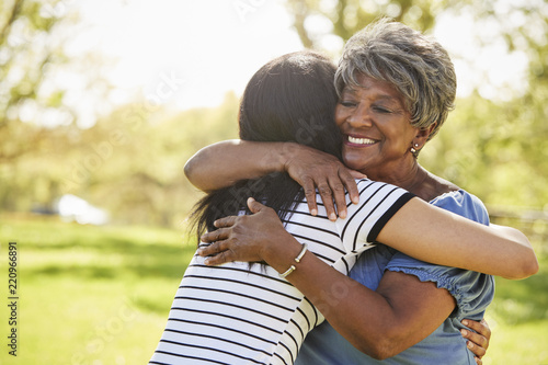 Fotografie, Tablou  Senior Mother With Adult Daughter Hugging In Park