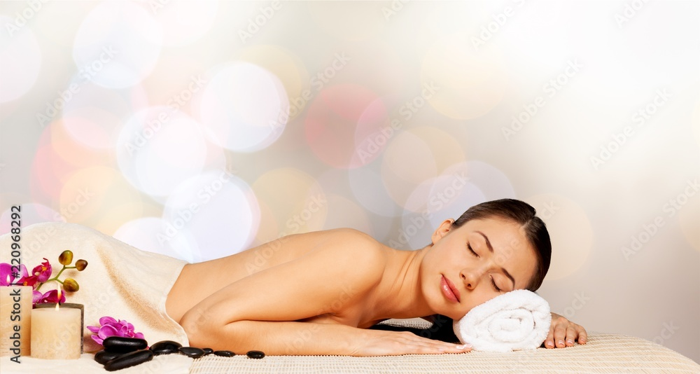 Fototapeta Beautiful young woman relaxing with stone massage at beauty spa