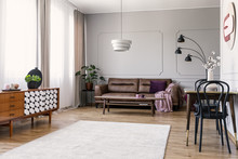 Wooden Cupboard In Bright Living Room Interior With Leather Sofa And Chairs At Table. Real Photo