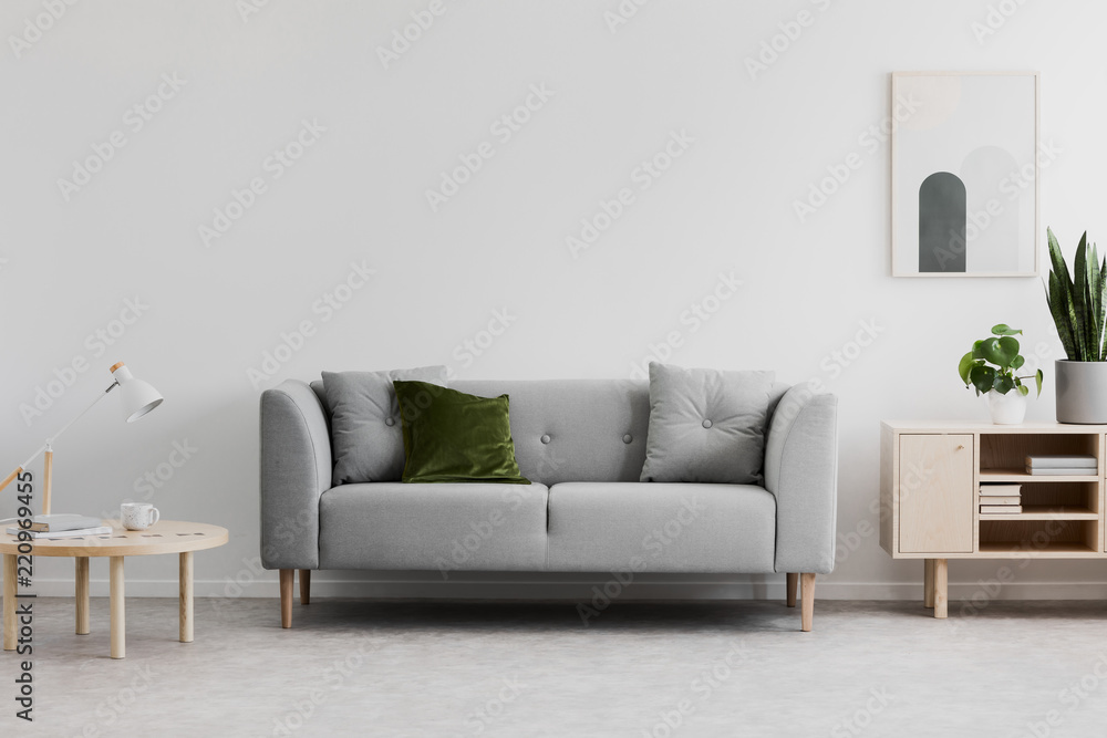 Fototapety, obrazy: Lamp on wooden table next to grey couch in white living room interior with poster and plants. Real photo