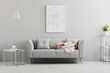 Leinwandbild Motiv Poster above grey sofa with pink blanket in living room interior with white lamp and plant. Real photo
