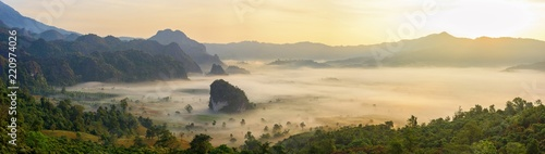 Beautiful sunrise view from the top. Panoramic misty mountain covered with morning fog and clouds.