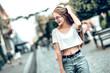 Leinwanddruck Bild - Lifestyle fashion concept.Young beautiful stylish woman walking in the street.