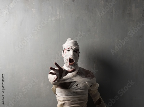 Terrorific mummy screaming on textured wall background Poster Mural XXL