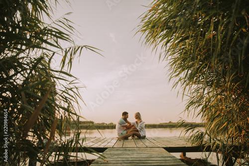 Obraz na płótnie Romantic couple sitting on the wooden pier on the lake