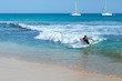 Boy surfing in blue ocean