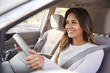 Young woman in car driving seat looking ahead, close up