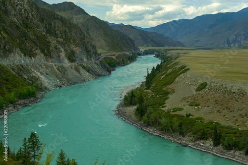 Spoed Foto op Canvas Khaki Landscape of the mountain chain of the Altai covered with green trees and rocks, with the turquoise Katun River and its rapids on a sunny summer day and a blue sky with white clouds. Tourist route.