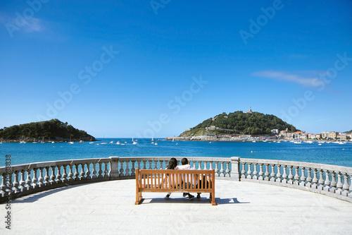Fototapeta premium Zakochana para siedzi na drewnianej ławce z widokiem na morze. Letni słoneczny dzień z błękitnym niebem. San Sebastian lub Donostia, Kraj Basków, Hiszpania