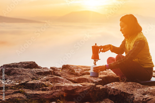 A woman traveler boils a geyser coffee machine and drinks a hot drink from the mug, admiring the colorful dawn with the fog in the mountains, camping and hiking in nature concept