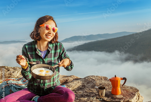 A woman traveler cooking and eating breakfast scrambled eggs and coffee at dawn in the misty mountains. Camping equipment and adventure concept