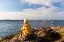 Boy Looks At The Sailboats From The Rocky Shore. The Concept Of Vacation. Copy Space For Your Text