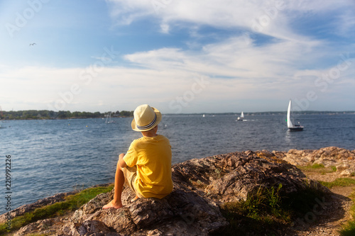 Fotografie, Obraz  boy looks at the sailboats from the rocky shore