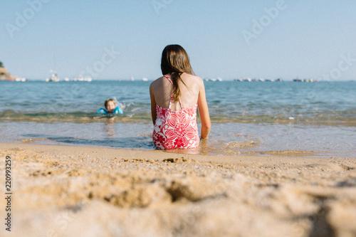 petite fille assise sur le sable au bord de la plage