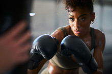 African Woman Boxing With Punching Bag In Garage Gym