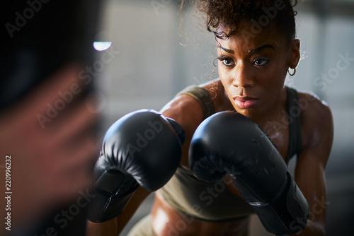 african woman boxing with punching bag in garage gym Tapéta, Fotótapéta