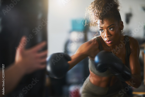Photo Stands Fitness african american woman striking punching bag in home gym