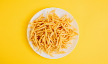 French Fries On Yellow Background. Potatoes Fries In The On White Plate. Flat Lay, Top View, Copy Space