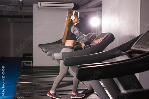 Spoed Foto op Canvas Fitness Young sports woman is working out in gym. Doing cardio training on treadmill.