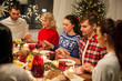 holidays and thankfulness concept - friends holding hands and praying while having christmas dinner at home